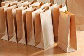Bolsas de papel en la mesa de madera en el sol de la mañana.