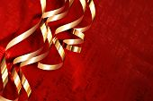 Holiday background image with shiny gold ribbons on red foil wrapping paper.  Macro with extremely shallow dof.  Copy space included.