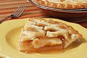 Slice of freshly baked apple pie on decorative plate.  Colorful tablecloth and whole pie in backgrou