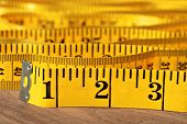 Bright yellow tape measure on wood.  Macro with extremely shallow dof.