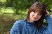 Retratos al aire libre de preciosa morena sonriente en suéter azul.  Close-up con poca profundidad dof.