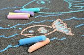Colorful sidewalk chalk with sketched fish in background.  Close-up with shallow dof.  Focus on foreground.