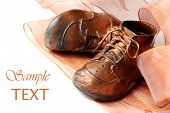 Vintage bronzed baby shoes with matching metallic ribbon on white background with copy space.