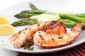 stock photo of lobster tail  - Closeup of delicious grilled lobster tails served with asparagus and bearnaise sauce - JPG