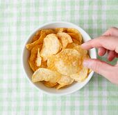 Snacking from the potato chips bowl