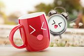 Red Cup Of Coffee And Alarm Clock With A Happy Smile On Wooden Table Against Natural Background In T poster