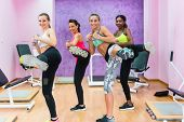 Cheerful fit women holding dumbbells, while doing a lateral leg raise during a group class of cardio poster