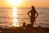 Pretty Young Model With Long Hair Tanning In Black Swimwear Against An Ocean And Sunset . Concept Of poster