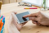 Businessman Touching Screen Of Smartphone Close Up. Touching Smartphone In Home Office On Wood Table poster