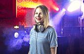 Smiling beautiful female dj in a disco