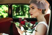 Beautiful Bride With Wedding Bouquet Sitting In Car. Trendy Bridal Bouquet. Perfect Bridal Makeup An poster