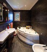Modern bathroom with large dark tiles. Nobody inside. poster