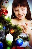 Little Smiling Girl Under A Christmas Tree