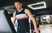 Caucasian Athletic Man Running In A Modern Gym On A Treadmill Doing Cardio Exercises. Young Handsome poster