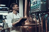 Brewer Standing Near Apparatus In Modern Brewery. Professional Brewer. Fermenting Beer. Metal Tank.  poster