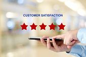 Man Hand Holding Smart Phone And Red Five Star Over Blur Background, Customer Excellent Rating Satis poster
