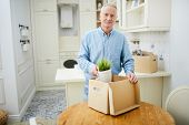 Mature man standing by wooden table and packing carton box with domestic stuff before relocation poster