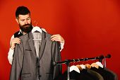 Man Looks For Clothes At Fashion Shop. Bearded Hipster Man Stands Near Rack With Clothes Against Red poster