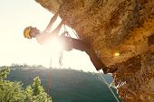 Picture Of Man Climber In Helmet Clambering Up Cliff. Sunflare Effect. poster