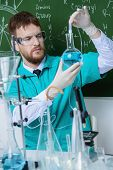 Smart man scientist making chemical experiments in the laboratory. Educational concept. Discovery.  poster