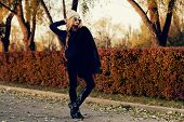 Autumn fashion shot. Trendy young woman in warm clothes posing in the autumn park. Youth style. poster