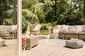 Pouf And Rattan Sofa On Wooden Patio With Hanging Chair In The Garden. Real Photo poster