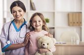 Friendly Doctor With Small Patient. Happy Girl And Doctor With Stethoscope. Joyful Nurse Plays With  poster