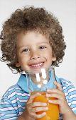 Happy little kid holding an orange juice glass,little kid drinking orange juice.