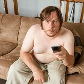 image of couch potato  - Man playing the lazy role of the couch potato - JPG