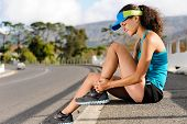 foto of injury  - runner with ankle injury holds foot to reduce pain - JPG