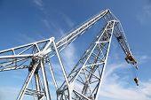 big white hoisting crane with hook at background of blue sky