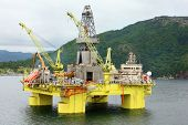 image of off-shore  - Ocean offshore oil rig drilling platform off near wooded shore of Stavanger - JPG