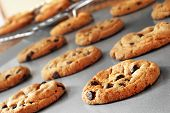 Freshly baked chocolate chip cookies on non-stick cookie sheet with cooling rack in soft focus in ba