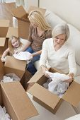 Female generations of a family, mother, daughter & grandmother unpacking boxes and moving into a new