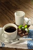 Powder stevia and stevia chocolate next to a cup of coffee without sugar