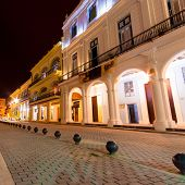 Colonial houses illuminated at night on the famous  Plaza Vieja square in Old Havana
