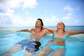 image of infinity pool  - Couple relaxing in swimming pool - JPG