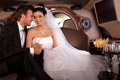 stock photo of fondling  - Beautiful young couple sitting in limousine on wedding - JPG