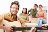 Amigos felizes, se divertindo juntos, tocando guitarra, sorrindo.
