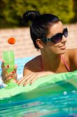 Attractive young woman in pool at summertime, drinking cocktail, looking away.
