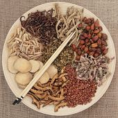 Traditional chinese herbal medicine selection on a round wooden bowl with chopsticks over hessian background.