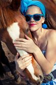 Beautiful young woman wearing blue dress with a horse outdoor.