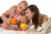 Young couple lying on bed with cup of tea