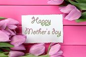 Beautiful bouquet of purple tulips and card on pink wooden background