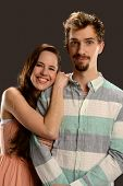 Young Couple smiling isolated on a gray background