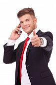 young business man showing thumbs up while speaking on the phone and smiling to the camera. isolated on white background