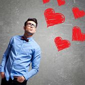 young business man looking up at some hearts