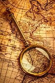 Vintage still life. Vintage magnifying glass lies on an ancient world map
