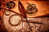 Vintage magnifying glass, compass, goose quill pen and a pocket watch lying on an old map.