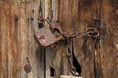 Old rusty padlock with chain on wooden door